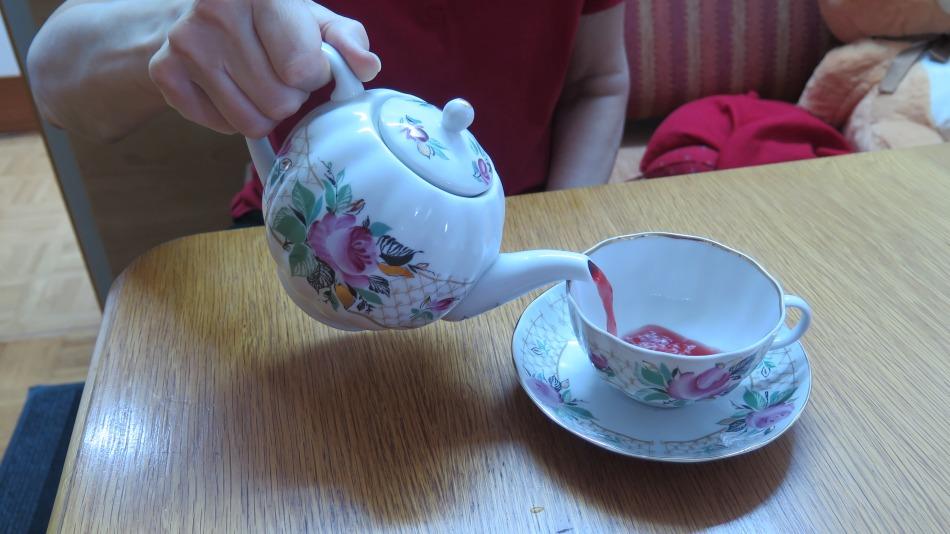 Am Tisch steht eine Tasse, die  mit heißem Tee gefüllt wird