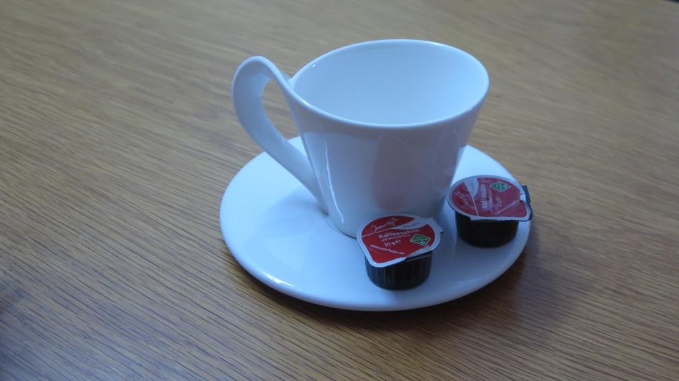 Kaffeetasse mit 2 Kapseln der  portionierten Sahne
