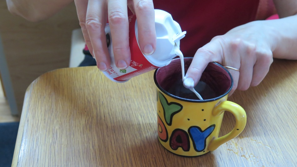 Über den Zeigefinger fließt die Sahne  in die Tasse.