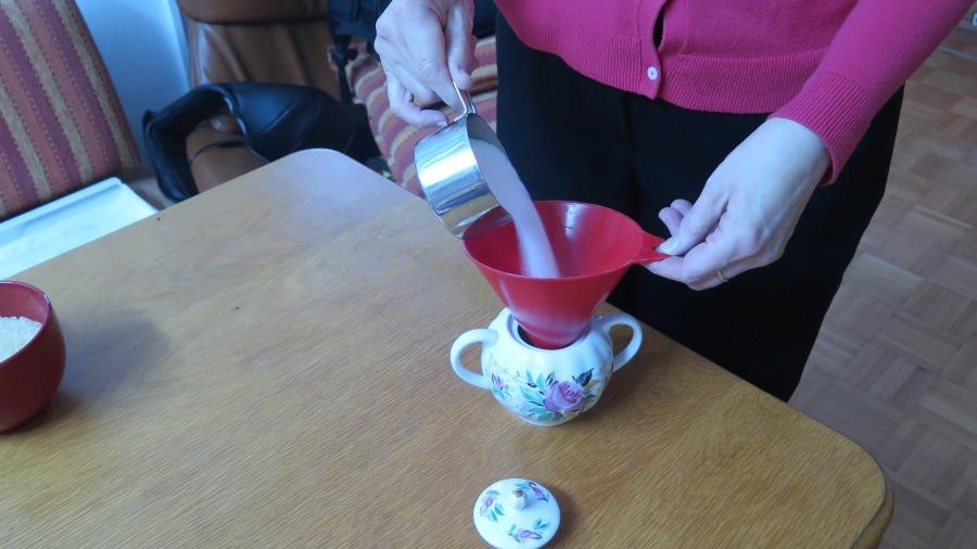 Die Zuckerdose wird über den Trichter mit Zucker gefüllt