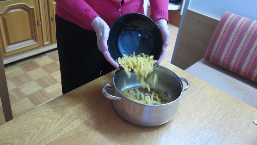 Nudeln gleiten aus einer Schüssel ins kochende Wasser