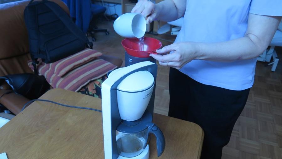 Kaffeemaschine wird über den Trichter mit Wasser angefüllt