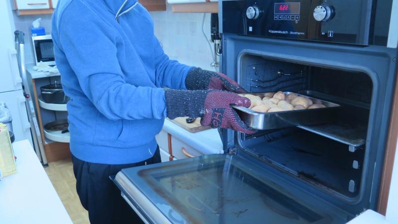 Auflaufform mit Kartoffeln wird in den Ofen geschoben