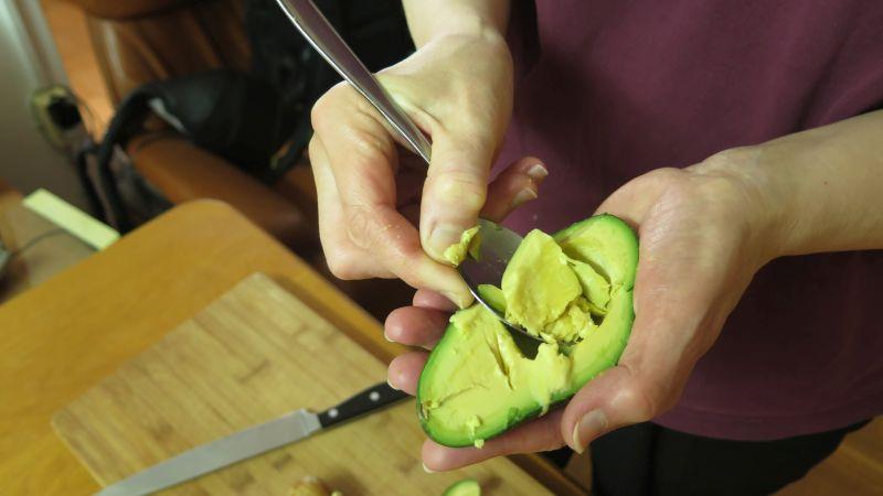 avocado wird mit dem löffel ausgehöhlt