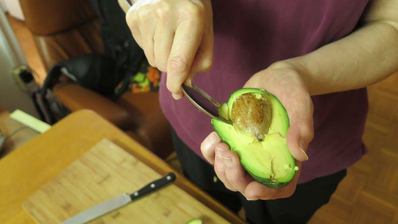 avocado kern wird mit löffel entfernt